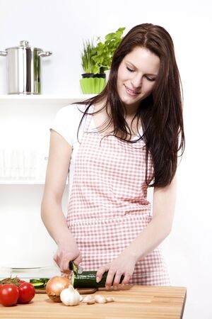 knife tomato: young woman in a kitchen cutting cucumber for salad