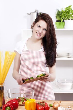 happy smiling young woman in a kitchen adding chopped paprika to her salad in a bowl photo