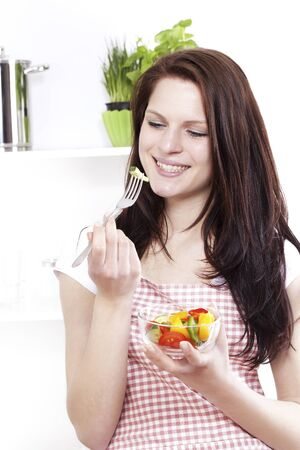 summer diet: pretty smiling happy woman in a kitchen about to eat her salad