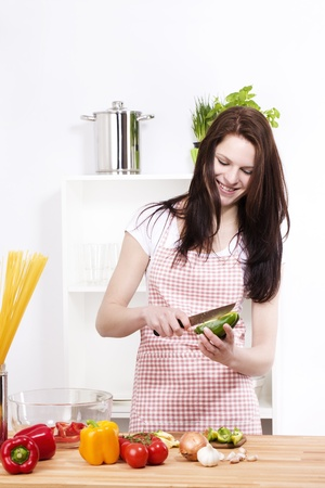 pretty woman in a kitchen chopping green paprika for salad photo