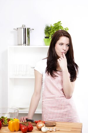 finger licking: young woman wearing a apron in her kitchen sucking her finger