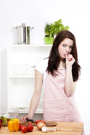 finger licking: young woman in her kitchen chopping vegetables sucking her thumb