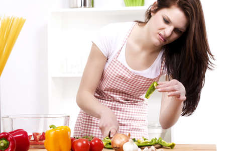 young woman is suspicious about the paprika she was chopping photo