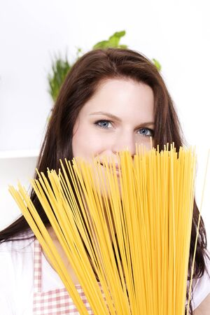 young pretty smiling woman is hiding behind some spaghetti photo