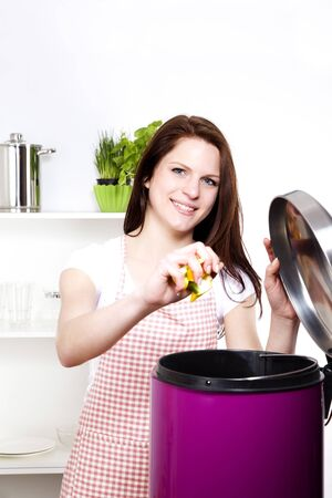 throwing: young smiling woman throwing away some organic waste Stock Photo