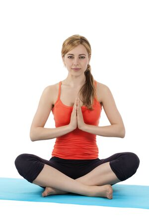 tailor seat: young fitness woman exercising yoga in tailor seat on a blue mat on white background