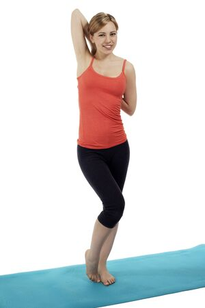 young happy fitness woman standing on a blue mat stretching her arms on white background Stock Photo - 14748331