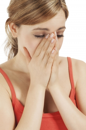 crying blonde woman holding hands to her face photo