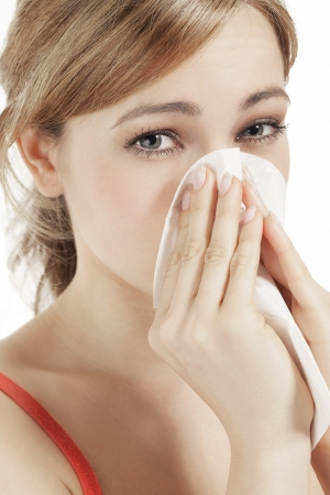 hayfever: young blonde woman suffering on hay fever sneezing with a paper tissue