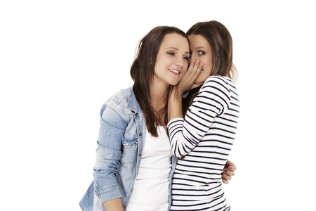 teenager whispering secrets to her friend on white background photo