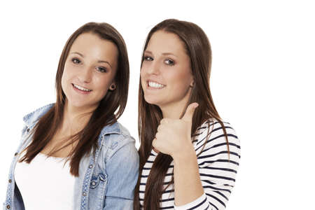 two happy teenager showing thumbs up on white background Stock Photo - 14898652