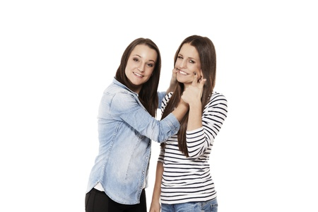 young teenager forcing her friend to laugh on white background Stock Photo - 14898618