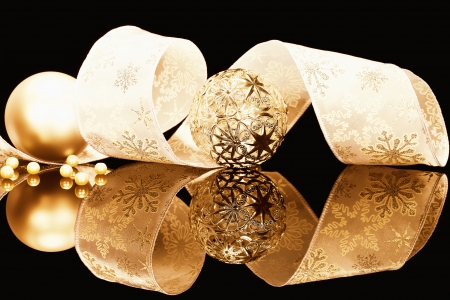 metal and dull golden christmas balls with ribbon on black mirror Stock Photo - 14932312