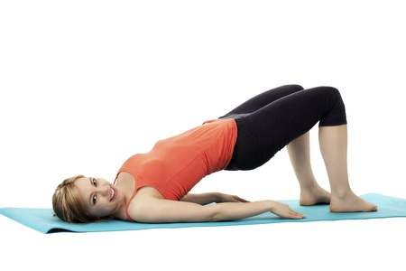 young happy fitness woman exercising on a blue mat on white background