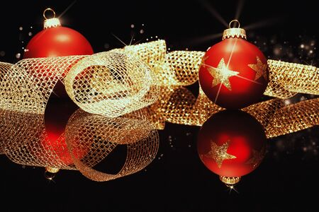 red christmas balls with glitter stars with golden metal ribbon on a black mirror  photo