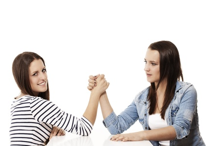 female wrestling: two female arm wrestling teenager on white background Stock Photo