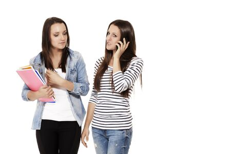 two teenager with exercising books and one is calling by smartphone on white background photo