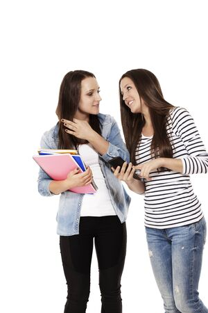 two communicating teenage students with a smartphone on white background Stock Photo - 15177711