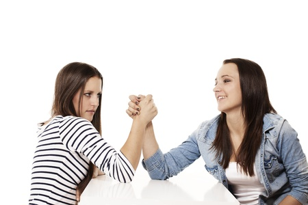 wrestle: one happy and one strained teenager arm wrestling on white background