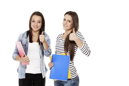 two female students with exercising books showing thumbs up on white background Stock Photo - 15177700