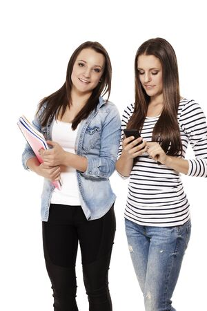 happy and busy students with smartphone and exercising books on white background photo