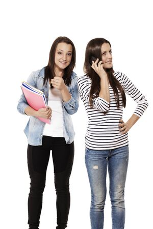 teenage student showing thumb up while her frind is on the phone on white background photo