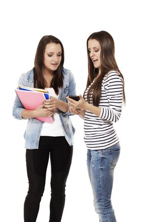 two pretty teenage students looking at a smartphone on white background photo