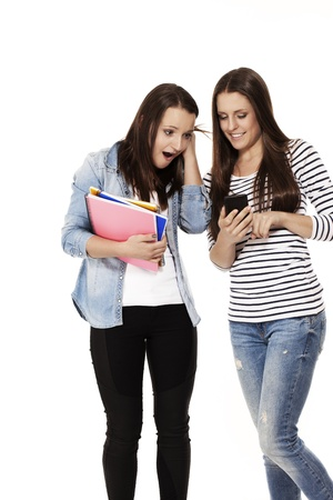 two teenage students are excited about their smartphone content  on white background