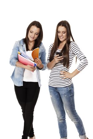 two busy students one with notepads one with smartphone on white background photo