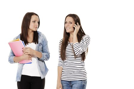 two pretty student friends calling by phone on white background photo