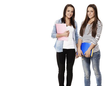portrait of two pretty student teenagers with note pads on white background photo