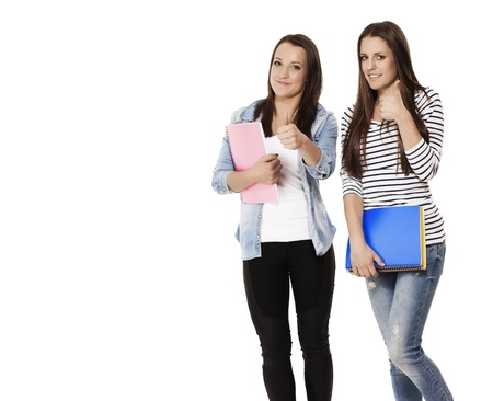 student female teenagers with notepads showing thumbs up on white background photo
