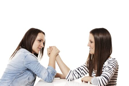 two pretty arm wrestling teenager on white background photo