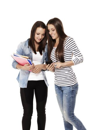 two happy teenage students looking at a smartphone on white background photo