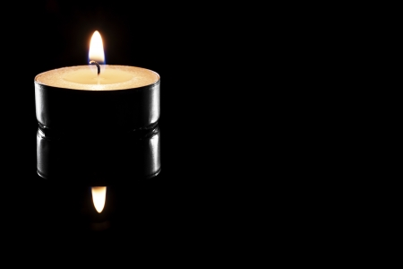 one burning tea candle on black reflective background