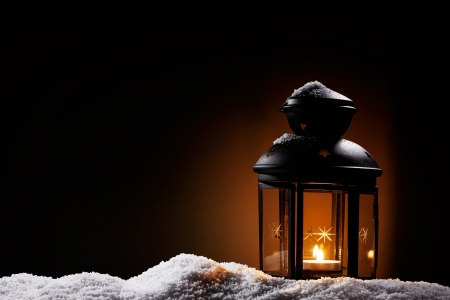 burning black vintage christmas lantern in the night on snow photo