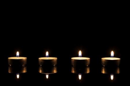 luz de vela: cuatro velas de té ardientes en un espejo negro sobre fondo negro