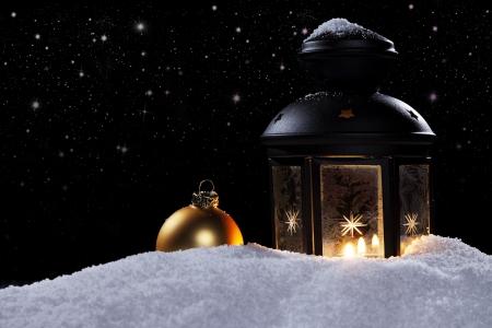 luz de velas: linterna congelado por la noche con estrellas y una de oro bola de Navidad en la nieve