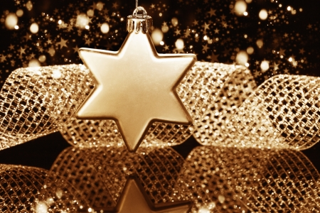 christmas ball in star shape in front of a metal ribbon and sparkling golden black background