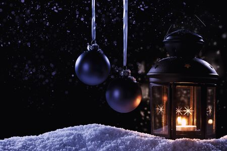 burning lantern at night  with two hanging blue christmas balls in snow at night Stock Photo - 15220575