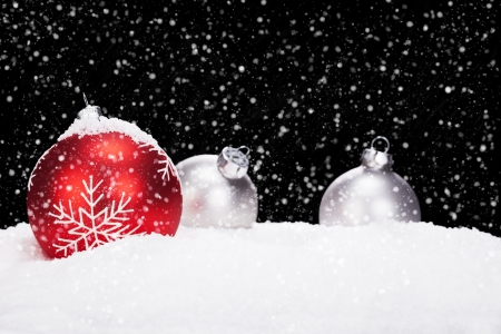 red and silver christmas balls in snow on black background while snowing photo