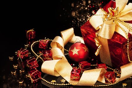 red christmas present with a red christmas ball and ribbons on black background Stock Photo - 15220584
