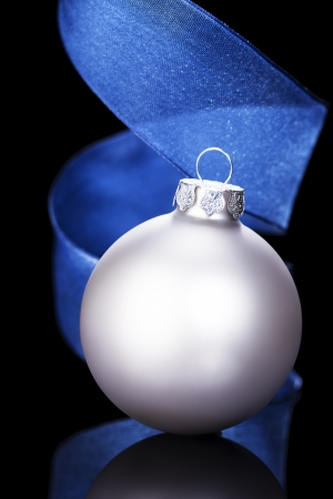 dull silver christmas ball in front of a blue ribbon on black background