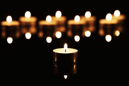 kerzen: ein brennendes Teelicht vor vielen brennenden Teelichter auf einem schwarzen Spiegel