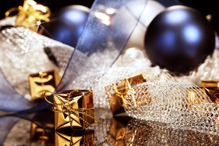 tiny shiny golden christmas present in front of christmas decoration with christmas balls and ribbons Stock Photo - 15220580