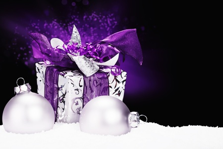 purple christmas present in snow with christmas balls and purple lightning on black background