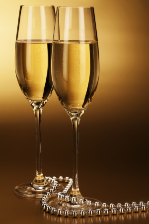 two glasses of champagne with a silver chain on golden background