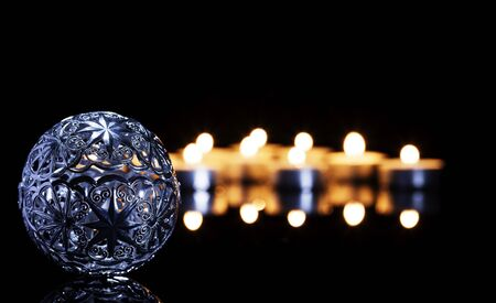 metal christmas ball in front of tea candles on a black mirror Stock Photo - 15579623