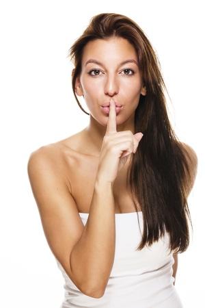 shush: beautiful brunette woman making shush sign on white background