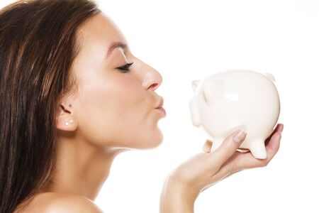 beautiful brunette woman about to kiss a white piggy bank on white background photo